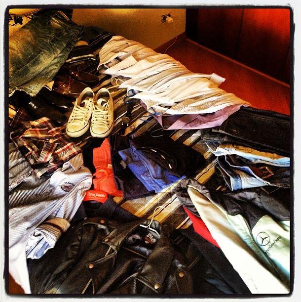 Os 33 itens do guarda-roupa minimalista do Alexandre sobre a cama.
