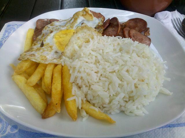 Prato com batata frita, arroz, carne e ovo