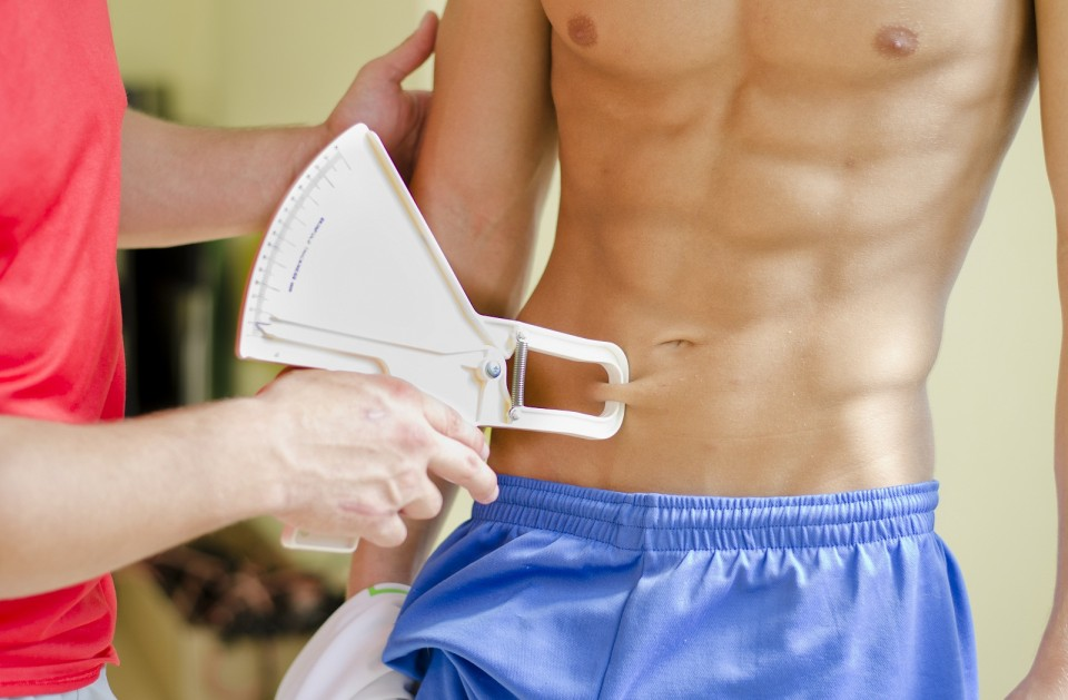 Personal trainer measuring shirtless muscular client's body fat